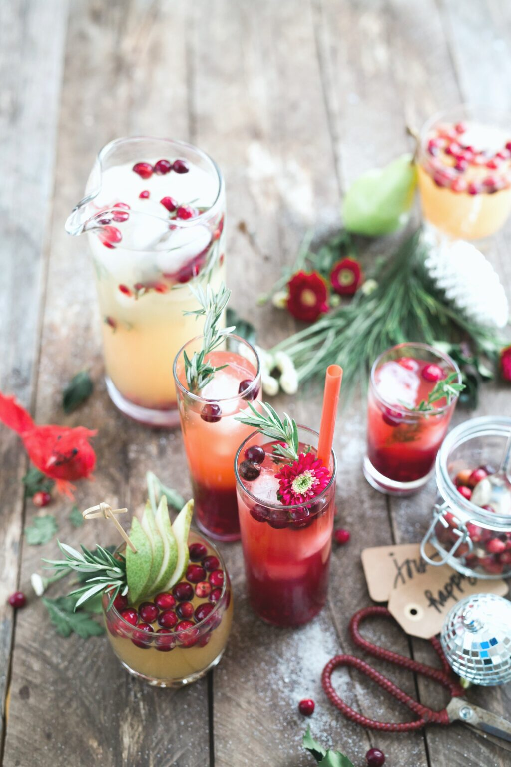 Glasses filled with beautiful cocktails and toppings that are festive for the Christmas season. Other Christmas items surround the drinks on a wooden table.