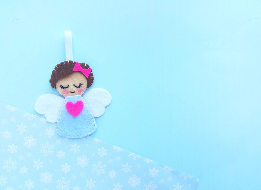Finished Angel ornament against a blue background.