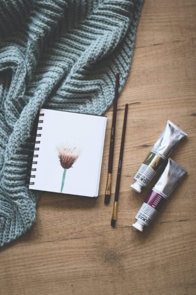 Throw blanket, notebook, and water colours on a wooden background.