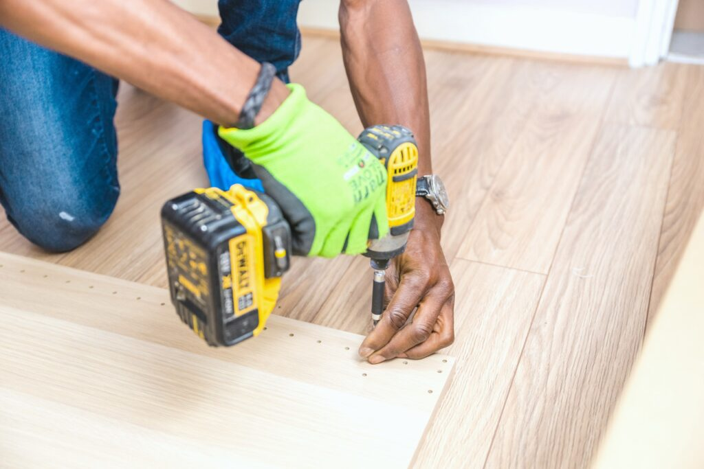 Man is doing a DIY project and is drilling into the floor. Only his arms and legs are visible.