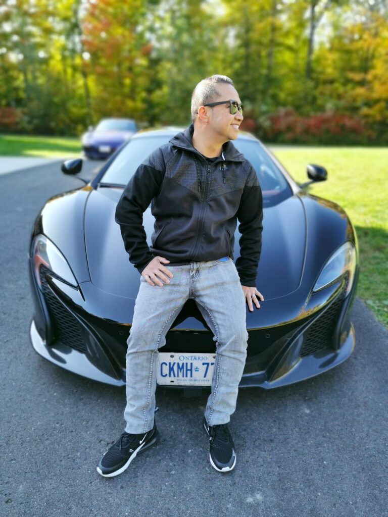 Darasak sitting on the hood of a McLaren. He is grinning ear to ear. Gifting family members for birthdays or special occasions can sometimes be tricky. It doesn't have to be. Check out these exotic car test drives in the GTA booked through #BreakawayExperiences. #giftideas #giftsforhim #boyfriendgifts #giftsforhusband