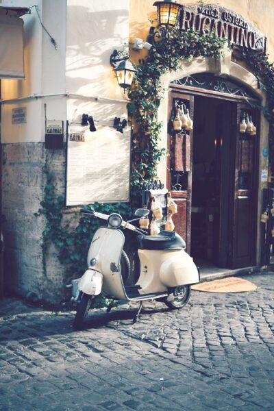 A motorbike parked in front of a restaurant on a European street.