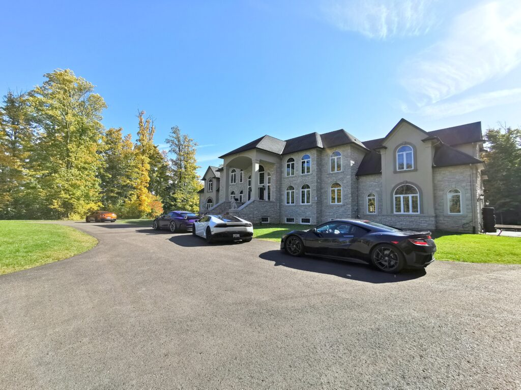 A beautiful private estate with super cars parked out front.