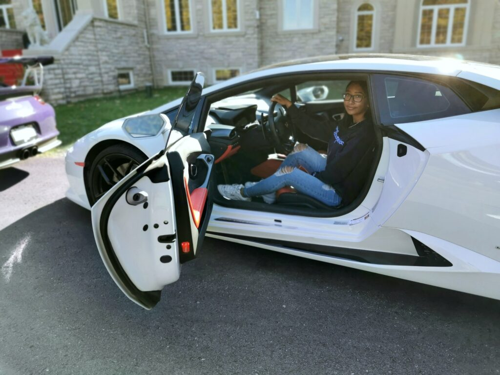 Gabby sits inside the Lambo.