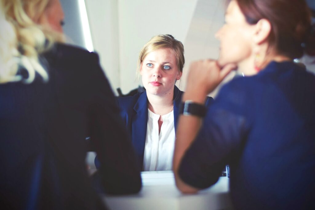 Woman looks at two people disappointed. They sit at a desk and look at each other. Woman is across from the other two women. When you're choosing a professional service, there's always a risk something can go wrong. Here is how to know when you've been let down by a service. #tips