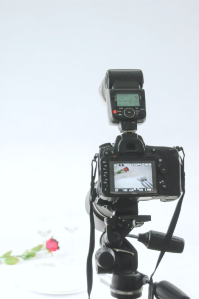 A camera on a tripod photographing two wine glasses and a rose.