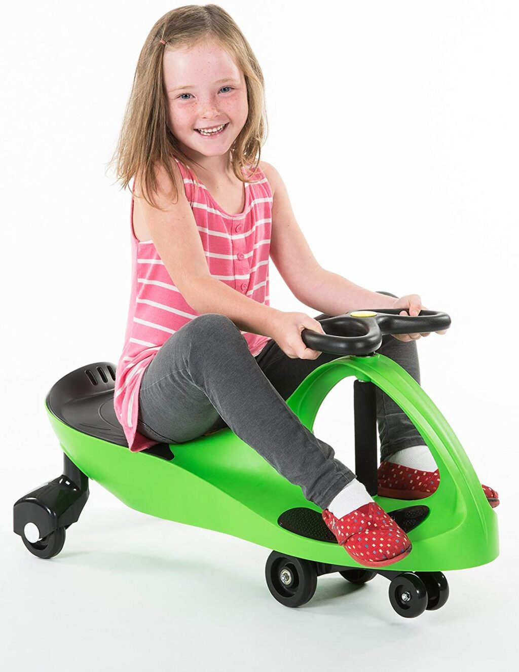 A little girl rides a Plasmacar, it is bright neon green.