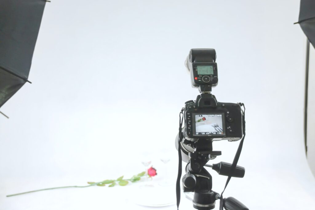A camera on a tripod photographing two wine glasses and a rose. When hiring an artist or photographer, picking the right production house is so important.