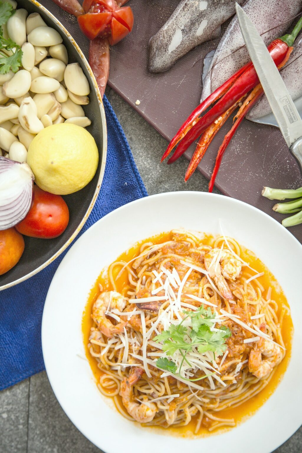 Shrimp pasta dish surrounded by ingredients to create dish.