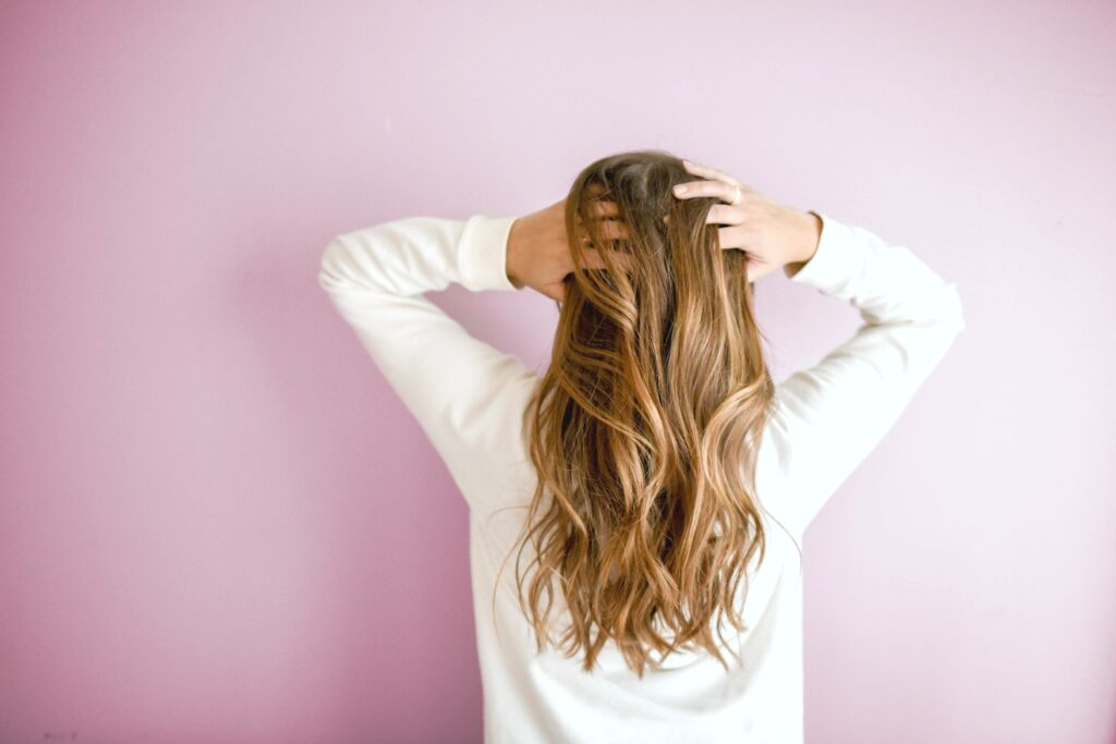 Girl stands towards a pink wall, with her hands to her head. Her hair is the main focus. Ways to tame frizzy hair will be discussed.