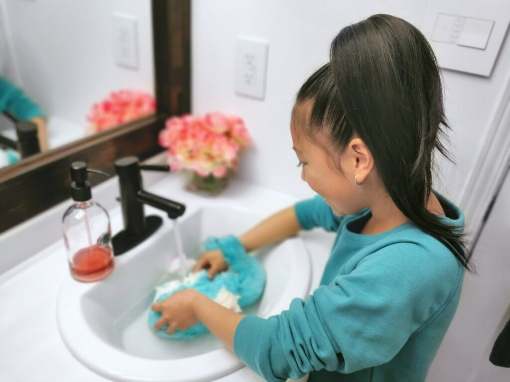 Mimi reveals her Scruff-a-Luvs, it's a cat! She washes him in the sink.