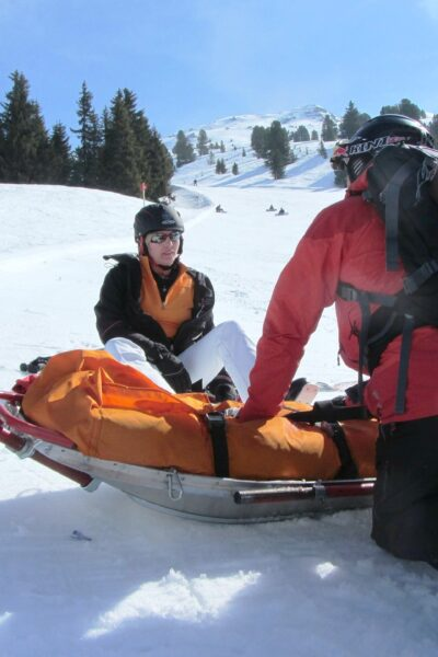 Skier that is injured is getting help from a medic.