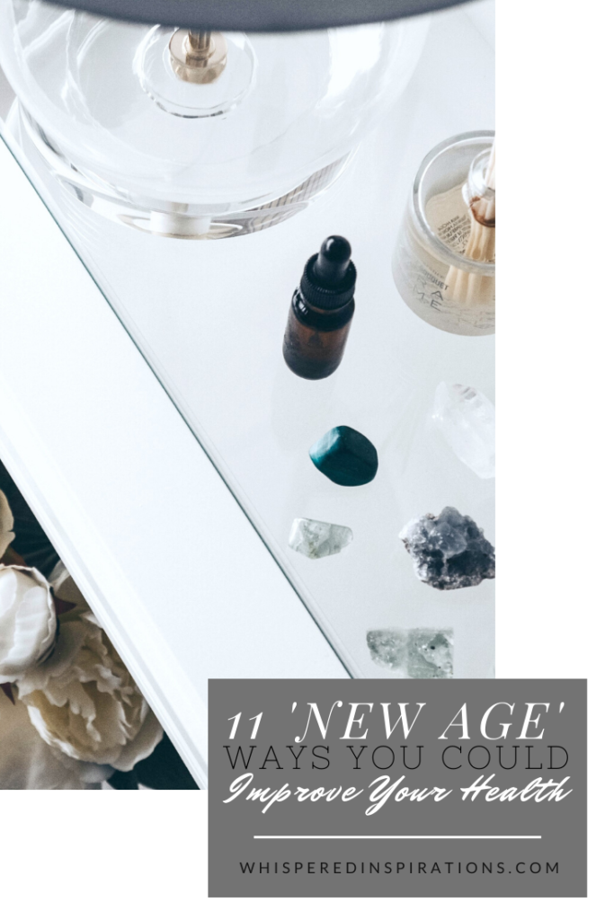"""A bedroom side table is adorned with a clear lamp, white flowers, and you can see crystals, essential oils, and incense. A banner reads, """"11 New Age Ways You Could Improve Your Health."""""""