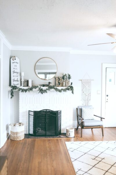 A beautiful living room. Decorated for the holidays. A fireplace and a mantle with hardwood floors.