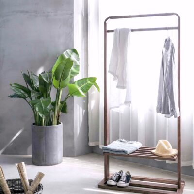 A gorgeous bedroom that has a wooden clothes rack and plants.