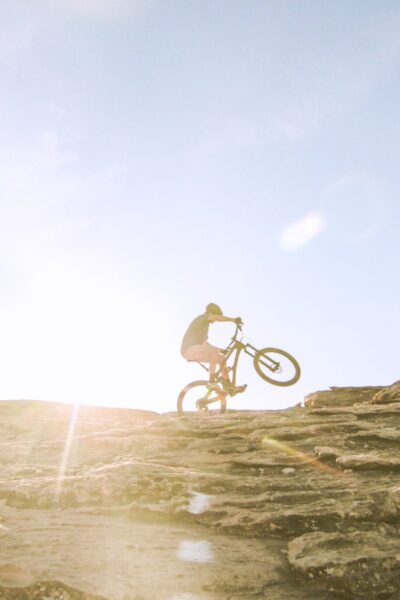 Cyclist on top of a mountain. The sun shines brightly behind him.