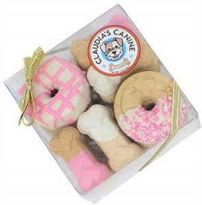 A box of dog cookies that are frosted and decorated with pink and white frosting.
