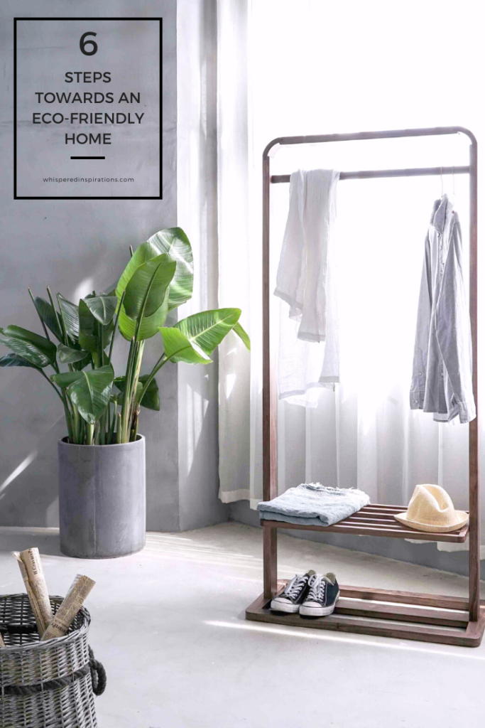 "A gorgeous bedroom that has a wooden clothes rack and plants. A banner reads, ""6 steps towards an eco-friendly home."""
