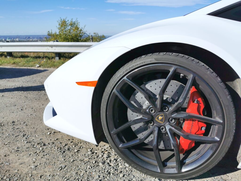 A close up of a white Lamborghini Huracan. Just the hoot and front tire is shown. Behind it is Lake Ontario and the hills of Hamilton.