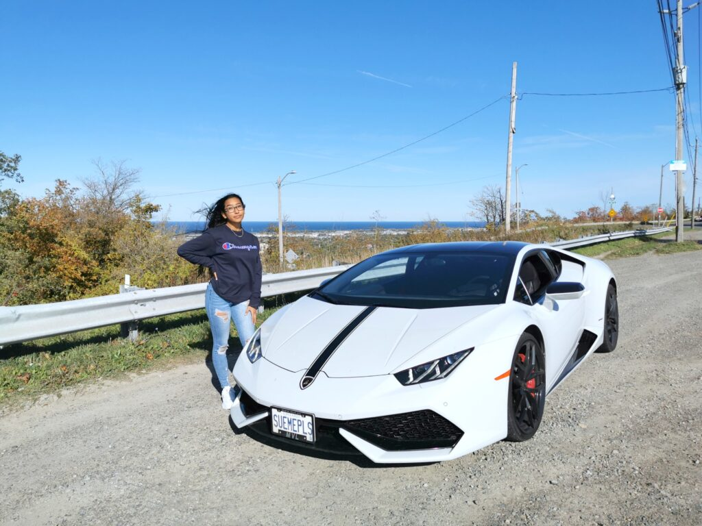 Gabby posing by the side of a road in Hamilton. She is next to a white Lamborghini Huracan.