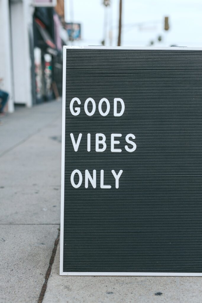 "A black and white letterboard on a street that says, ""Good Vibes."""