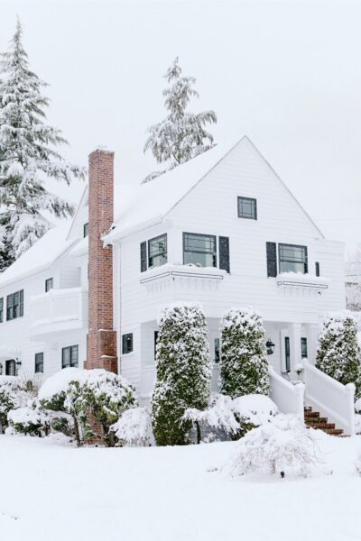 A beautiful older home, covered in snow. The snow covers everything around it, including evergreen pines behind the home. A red chimney pops out in the sea of white.
