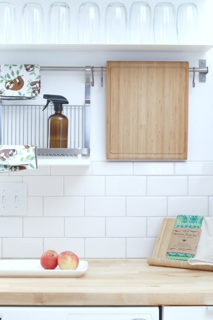 A kitchen is shown, against subway tiles, you can see a shelf with cleaning products and a cutting board.