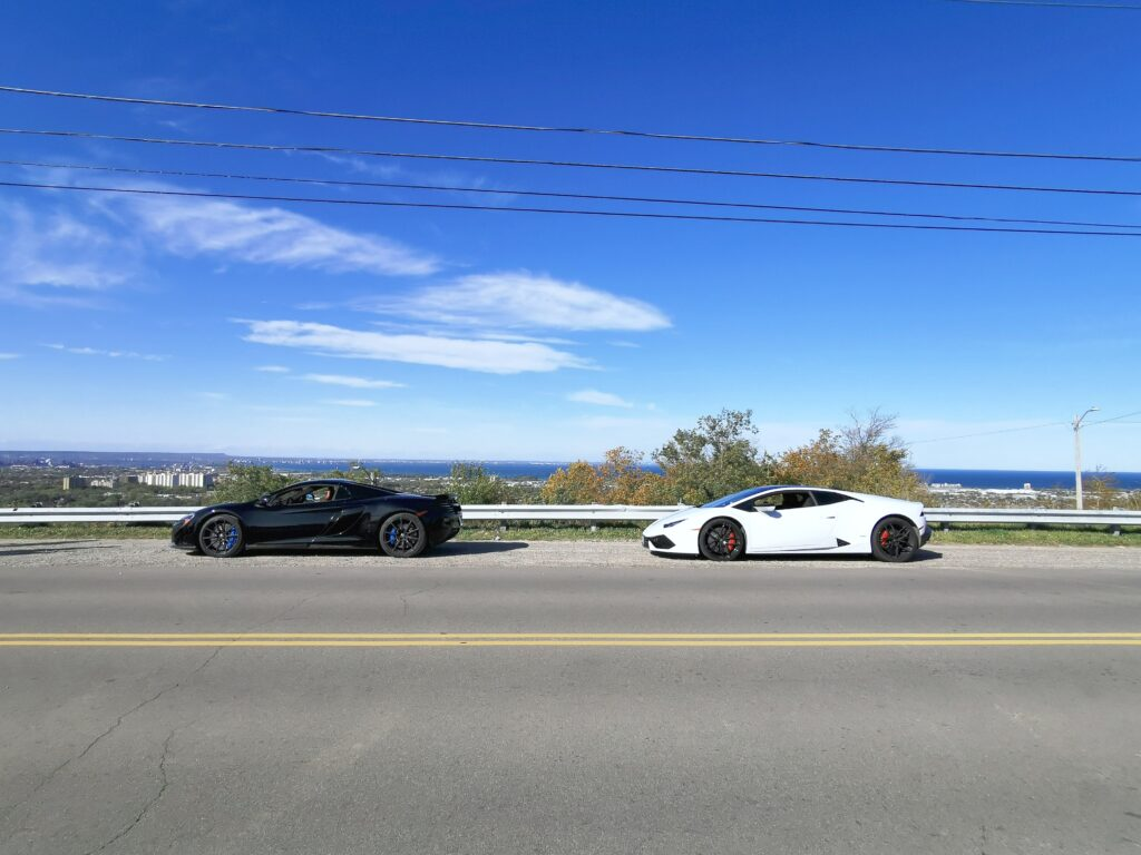 The McLaren and Lamborghini Huracan on a hill top with Lake Ontario and the Hamilton hills in the background.