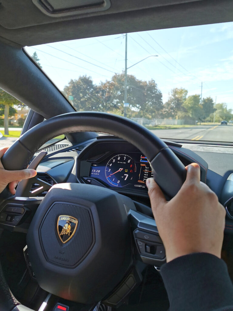 Nancy holding the steering wheel of a Lambo Huracan.
