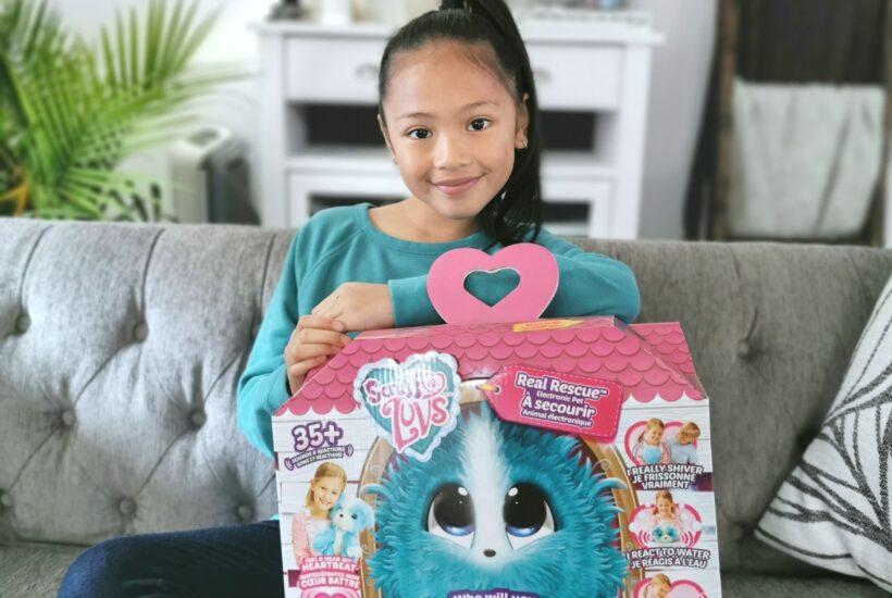 Mimi smiles while holding a Scruff-a-Luvs box.