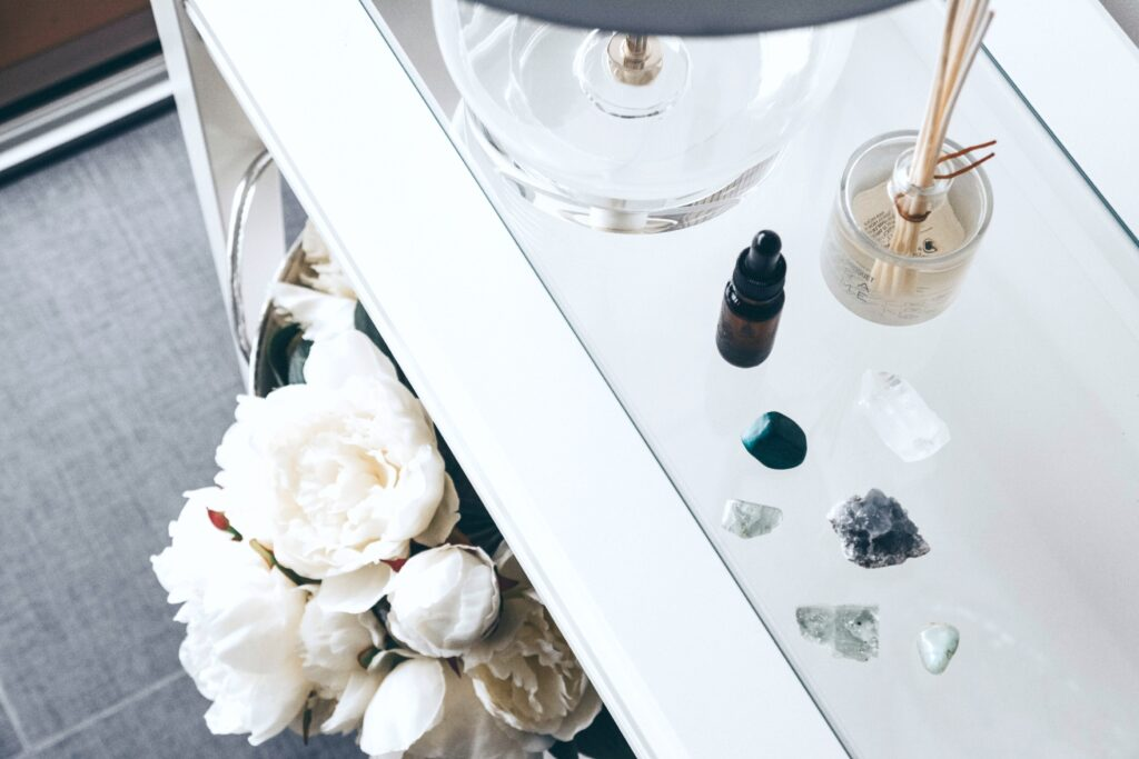 A bedroom side table is adorned with a clear lamp, white flowers, and you can see crystals, essential oils, and incense.