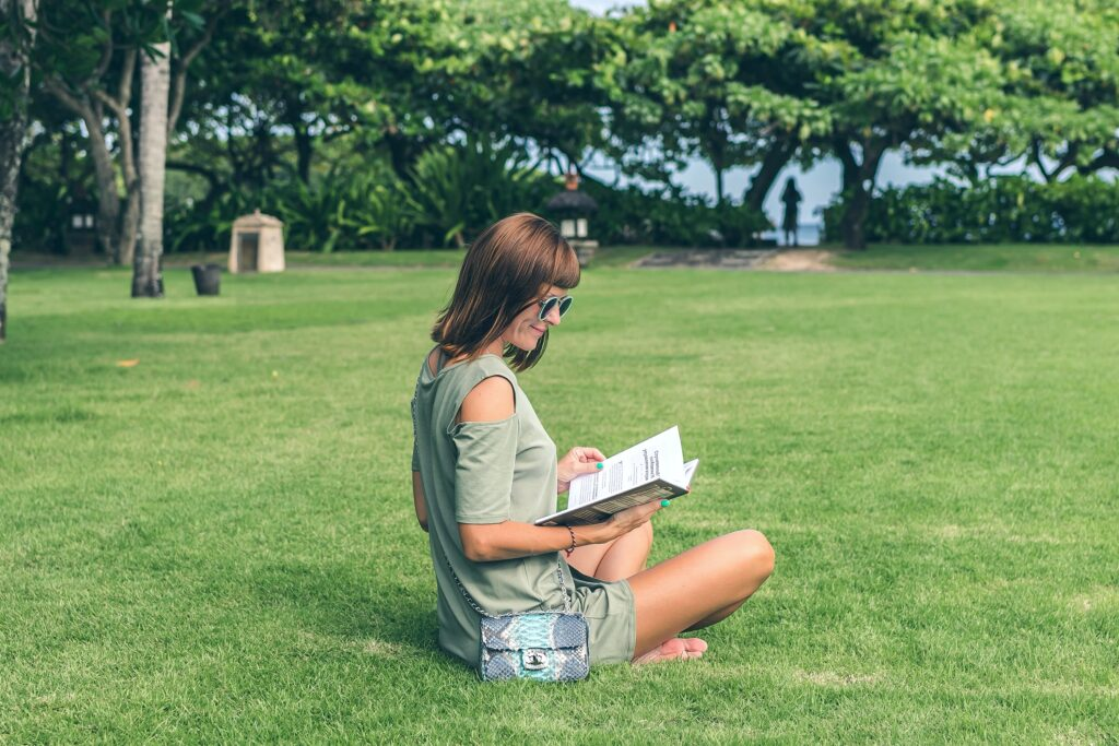 An older woman sits on a lawn reading a book and studying.  There are many reasons why you may think about going back to school. Like stability and securing a better future for your family. Use these tips! #tips