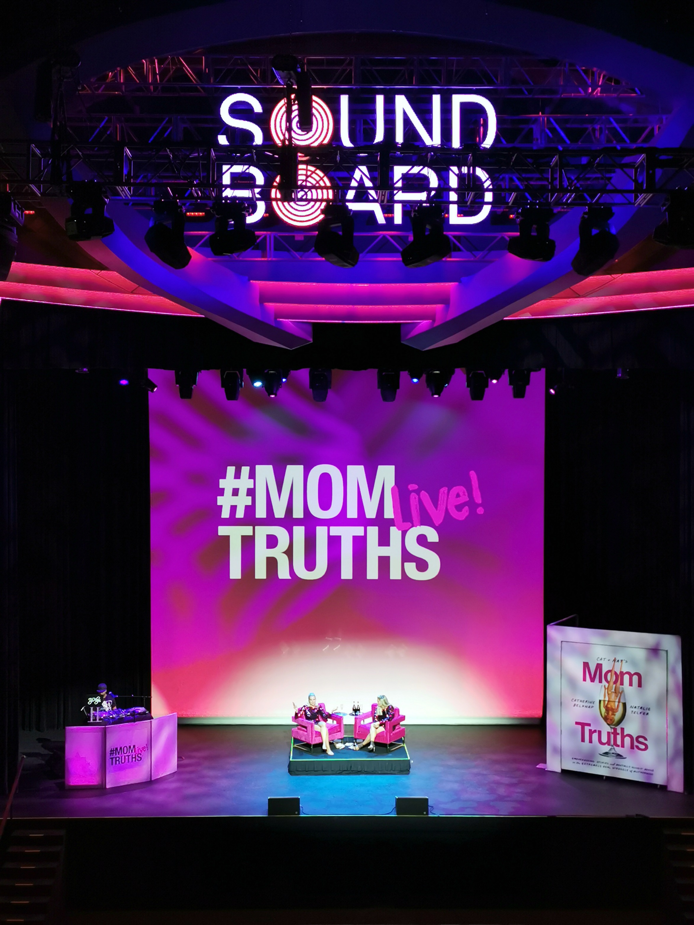 The #MOMTRUTHS Live show, Cat and Nat sit in lounge chairs center stage.