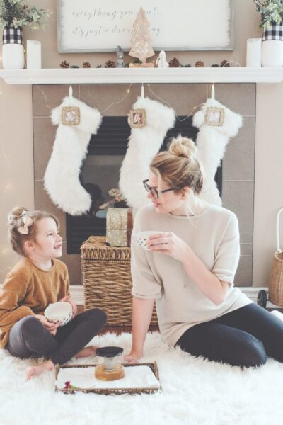 A woman and her daughter sit in front of fireplace, drink hot chocolate, and smile. Christmas stockings are hung behind them.