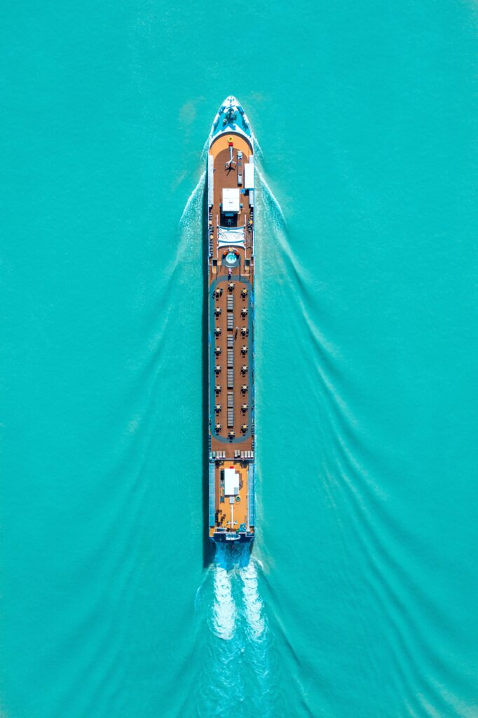 A cruise ship is seen on turquoise water and from birds eyes view.