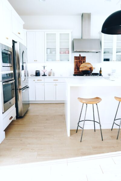 A white kitchen with black fixtures and natural wood stools.