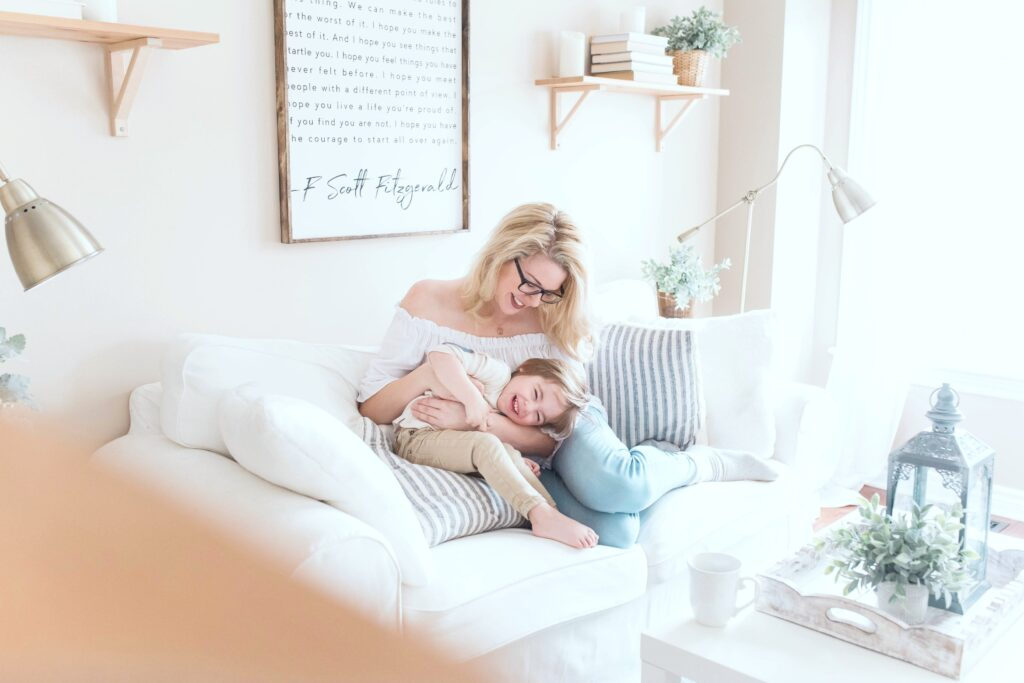 Woman and her son sit on the couch in their warm and inviting living room.