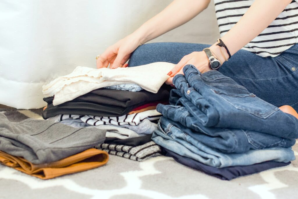 A woman folds clothes and is getting ready to pack.
