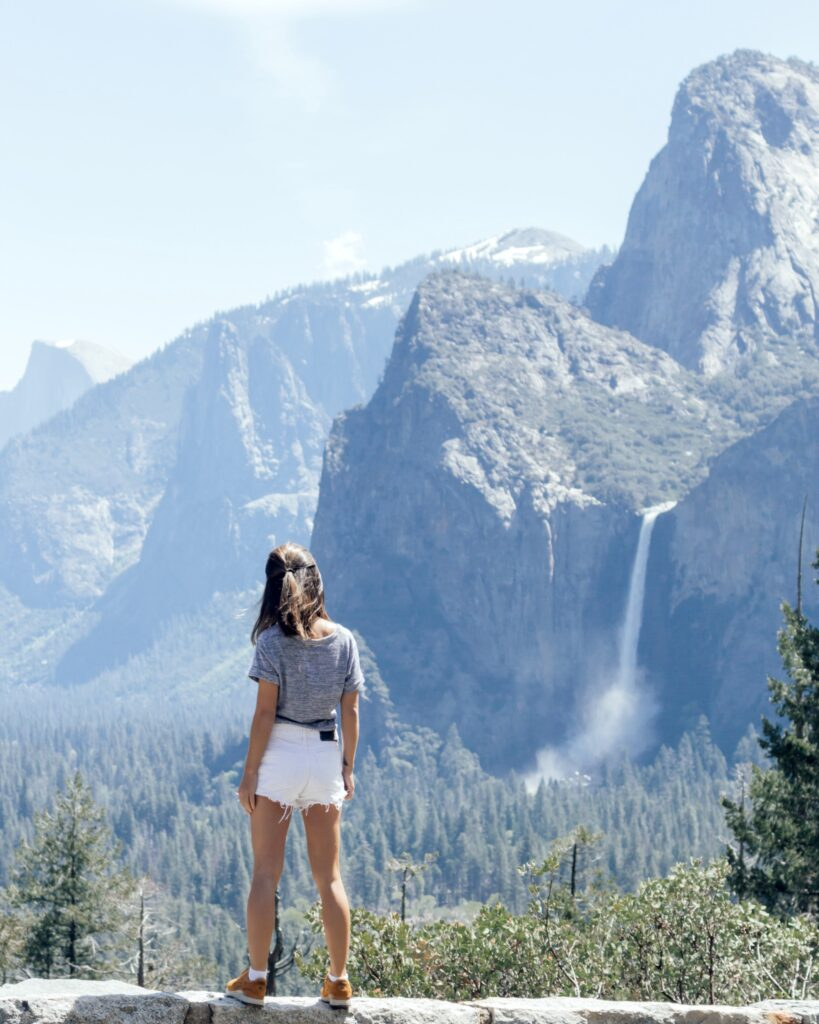 Girl hiking, mountain and waterfall is in front of her in distance.