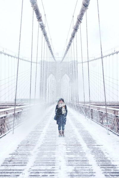 A girl stands and smiles on the NYC bridge. It's a cold, windy, winter wonderland.