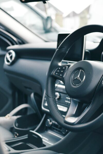 A look of an interior of a Mercedes-Benz. The steering wheel is shown.