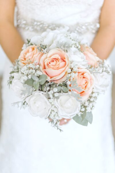A bride holds white, coral, and beige roses in a bouquet. Her arms are only visible.