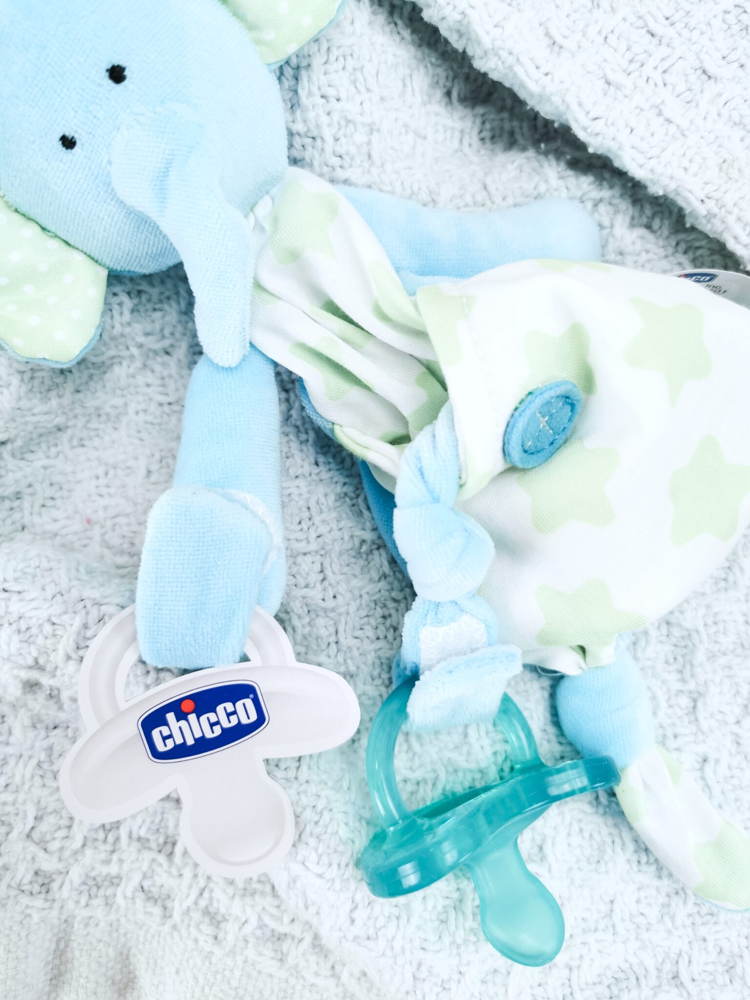 A blue blanket with a cute little teddy that holds the Chicco pacifier.