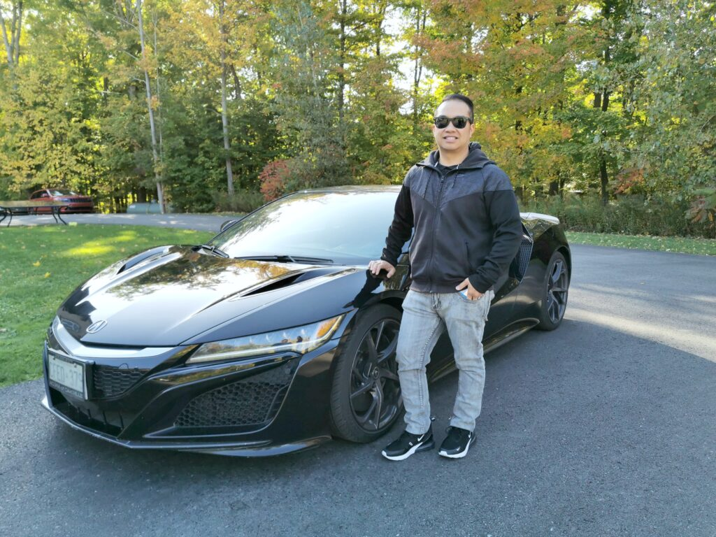 Darasak stands in front of an Acura NSX. This is for a super car test drive experience with Breakaway Experiences.