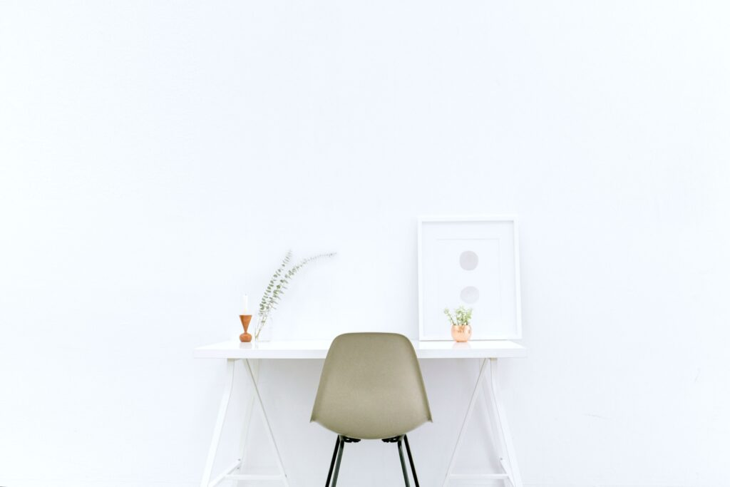 A white room with a white desk, a brown chair, and aluminium frame on top of desk.