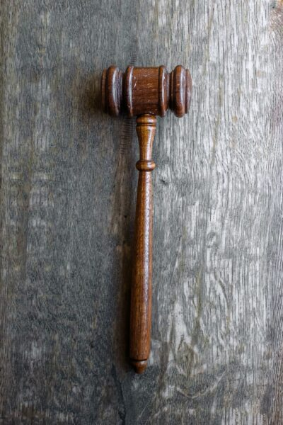 A gavel rests on a grey wooden top.