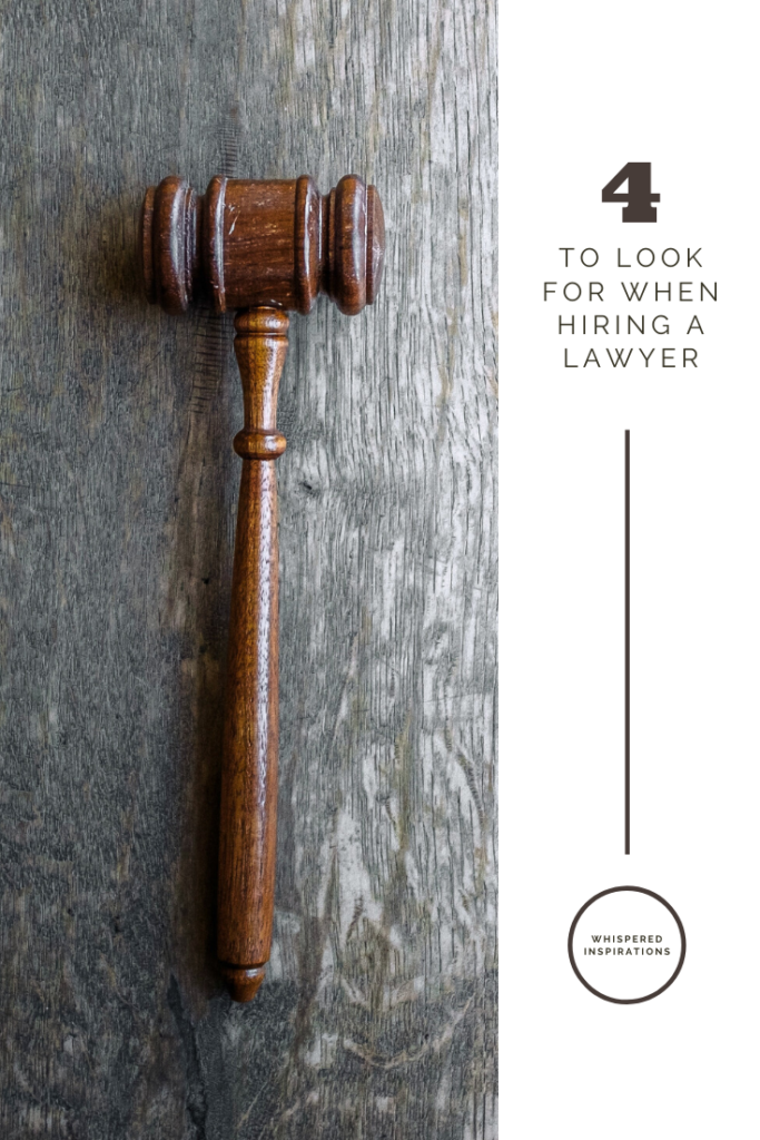 """A gavel rests on a grey wooden top. A banner reads, """"4 things to look for when hiring a lawyer."""""""