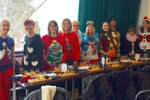 A group of women in ugly Christmas sweaters doing a food tour in Niagara.