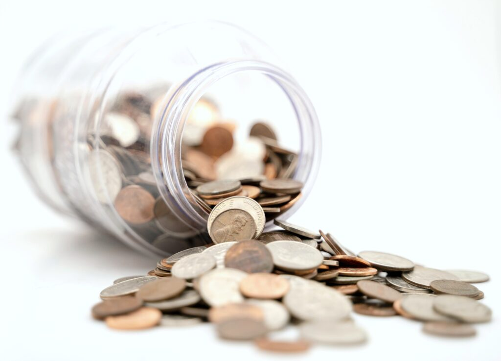 A jar is filled with coins and is on its side, while the coins spill out.