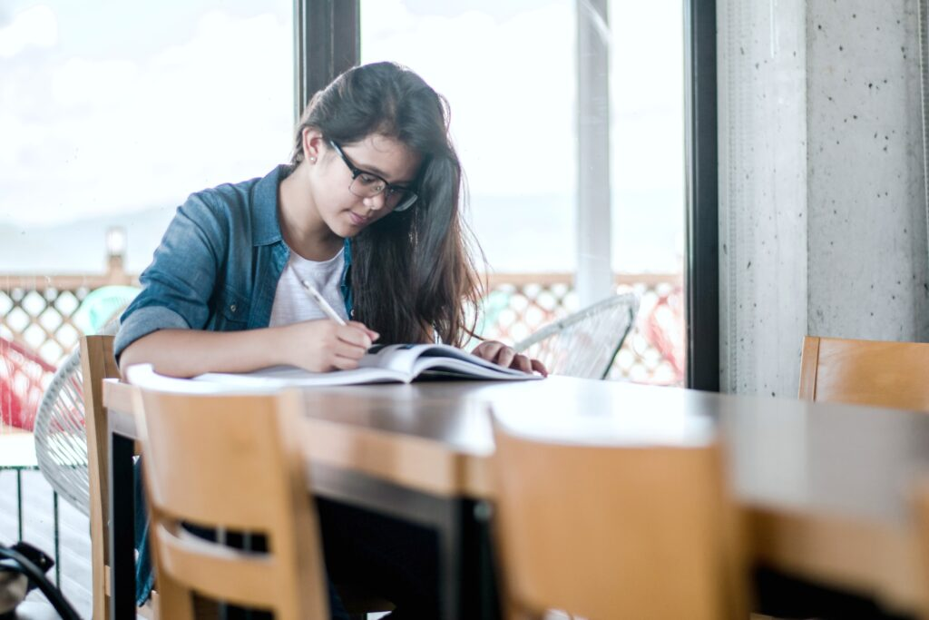 A student sits in a library by herself, studying for the SAT test.